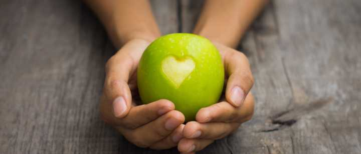 hands holding green apple with heart cut out
