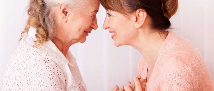 elderly mother and daughter holding hands, smiling face-to-face with foreheads touching