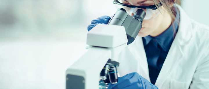 female lab worker looking into microscope