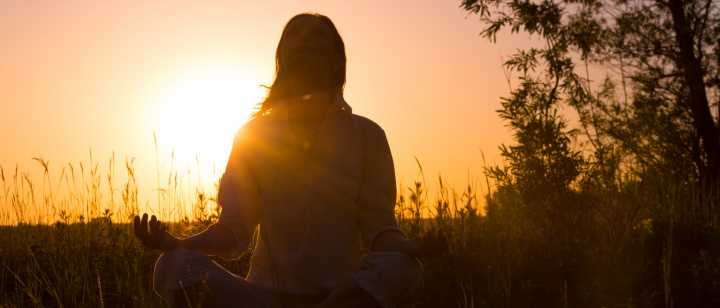 woman meditating in front of sunset