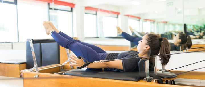 women on pilates reformer