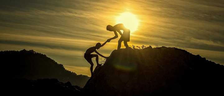 a teenager helping another teenager climb a mountain