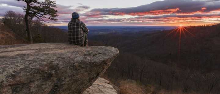 man sitting reflecting on rock ledge at sunset