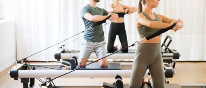 Group of people exercising on pilates reformer