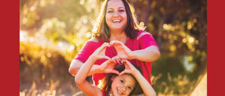 mother and daughter forming heart with hands