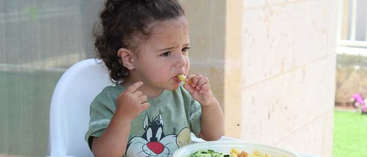 Toddler eating in a high chair
