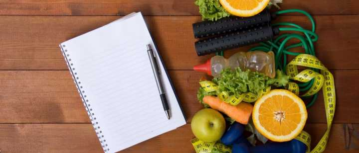 Notepad, vegetables, fruits and exercise equipment