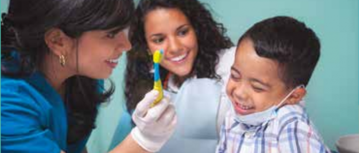 Dentist helping child with toothbrush