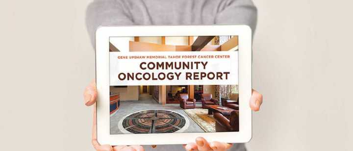 Woman holding ipad with Commmunity Oncology report cover on screen