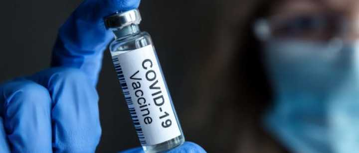 technician holding a vial of covid vaccine