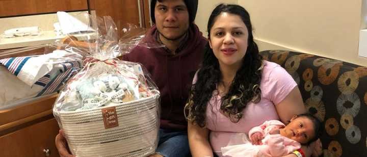 Father, Christian Meraz, Mother, Mayra Silva, and first baby of the new year, Leah Alessandra Meraz, with a gift basket donated by Tahoe Forest Health System Foundation's gift shop, The Gift Tree