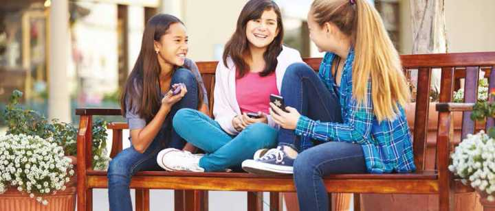 three smiling preteen girls sitting together on bench