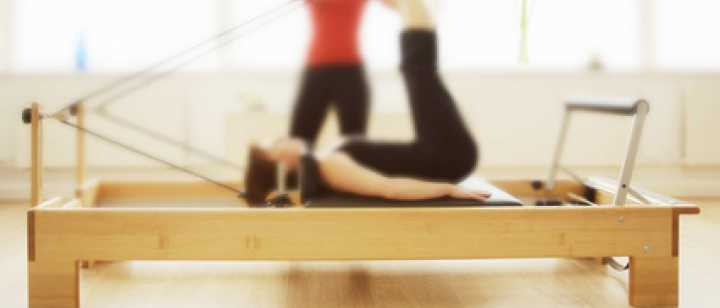 Woman exercises on reformer while instructor assists