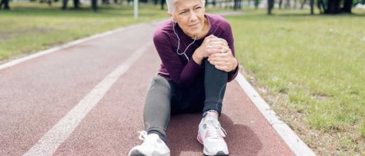 woman sitting on track field holding her knee
