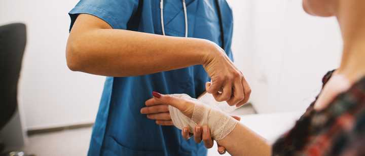 Doctor bandaging a patient's injured wrist