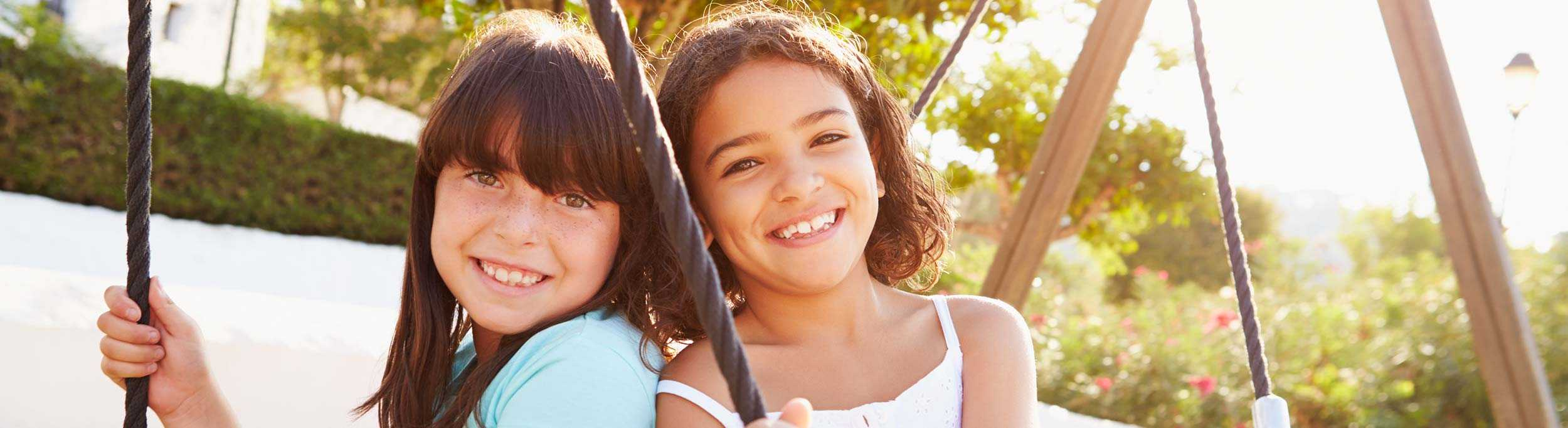 Two girls smiling on a tire swing